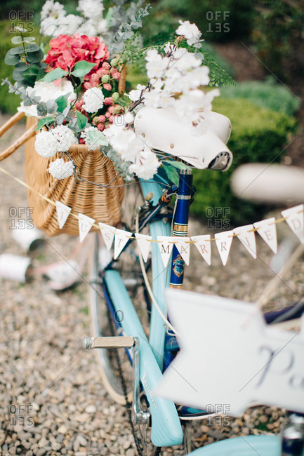 Blue bicycle adorned with a basket of flowers and a Just Married banner bunting
