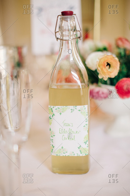 A bottle of Elderflower Cordial on a table next to a flower arrangement