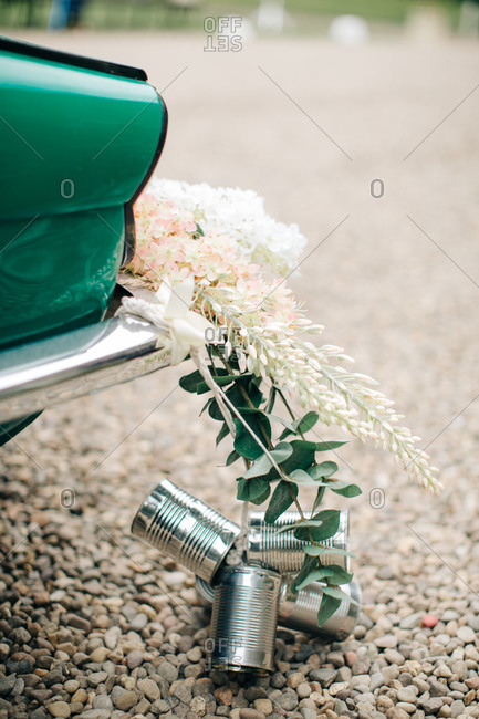 Wedding decoration of tin cans and flowers behind a car for a couple just married