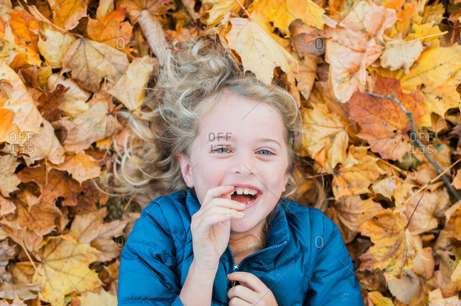 Little girl lying in a pile of leaves