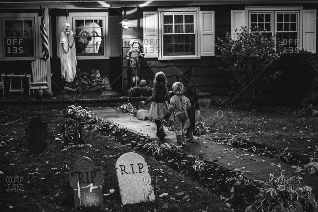 Children walking up to a spooky house on Halloween