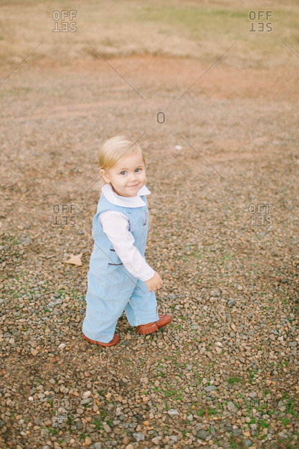 Baby in overalls and moccasins walking on gravel path