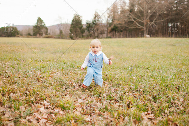 Baby walking in field with autumn leaves