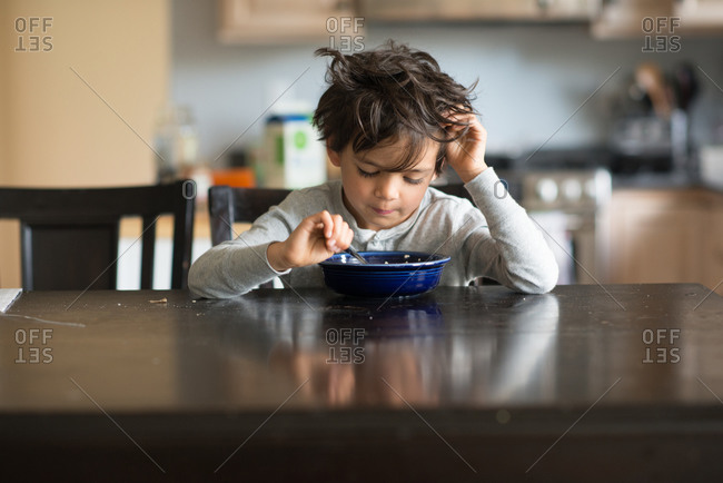 Young boy with bedhead at the breakfast table