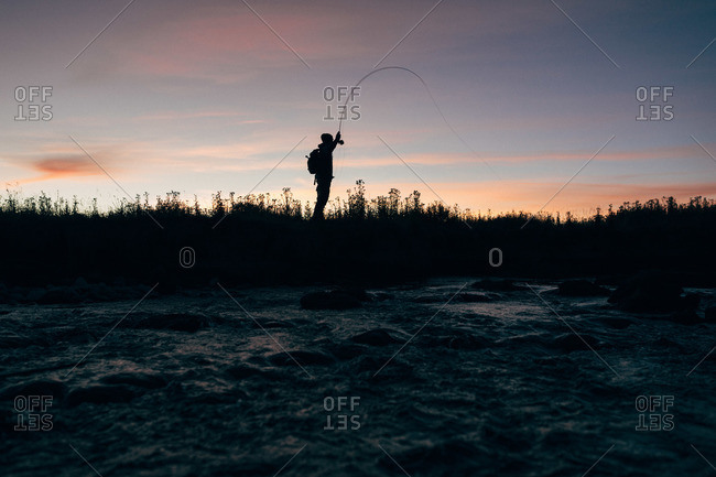 Silhouette of man fishing at sunrise