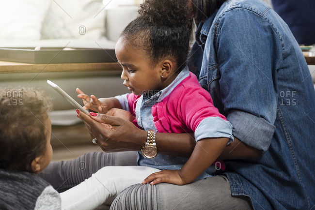 Mother holding young daughter in lap and using a digital tablet while infant son plays at her feet