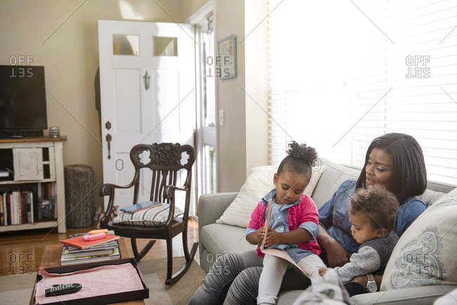 Mother sitting on the couch reading with her children