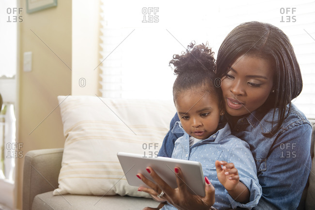 Mother holding young daughter in lap and using a digital tablet