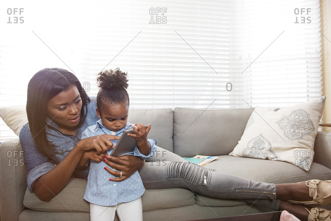 Mother helping young daughter use a digital tablet