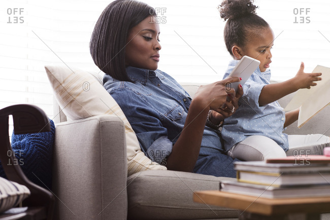 Mother sitting on the couch using a digital tablet while her young daughter reads