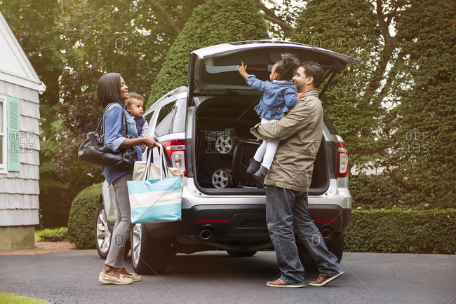 Parents with children standing behind the family SUV