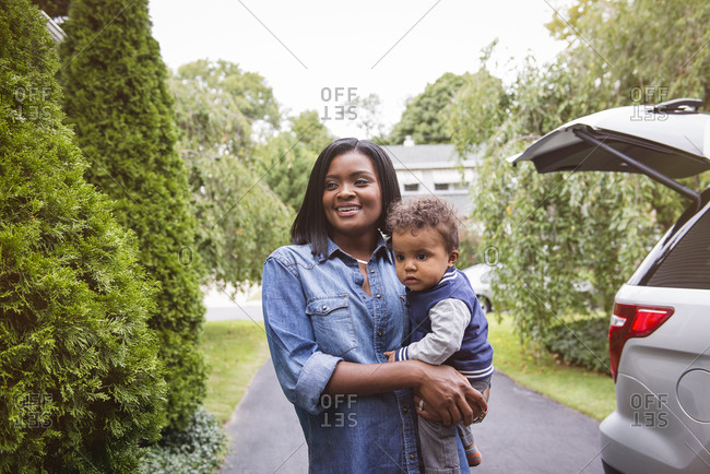Smiling mother standing next to family SUV and holding infant son