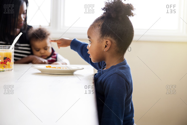 Little girl standing at the edge of the table and pointing at her snack