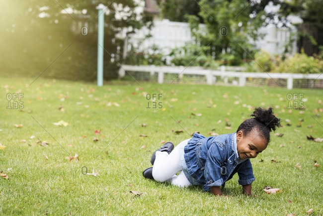 Little girl crawling in the grass