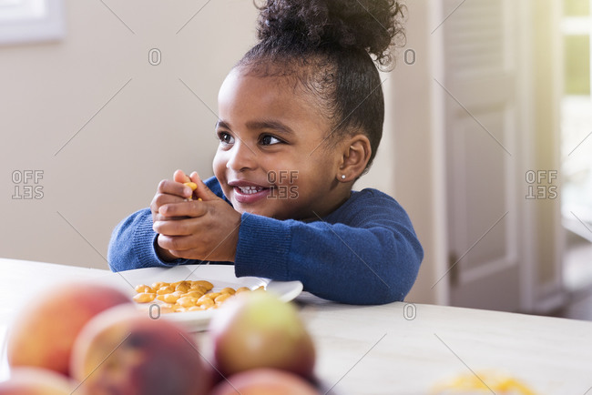 Little girl clutching a handful of cheese snacks