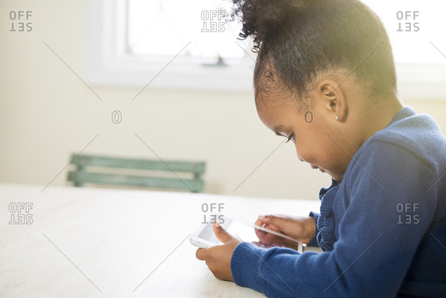 Little girl using a digital tablet at the table
