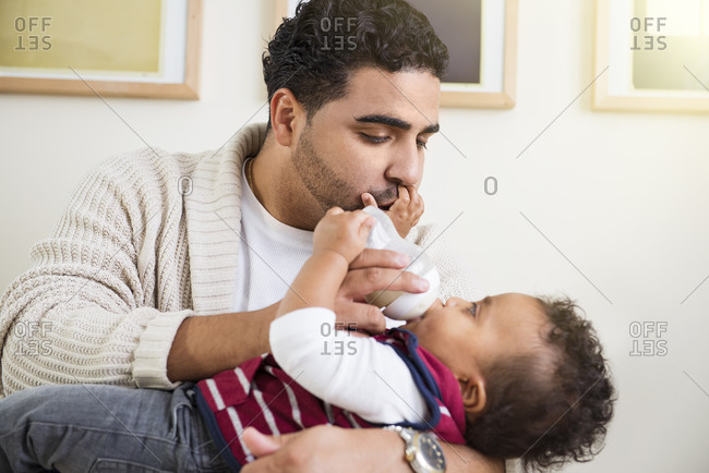 Father bottle feeding his infant son