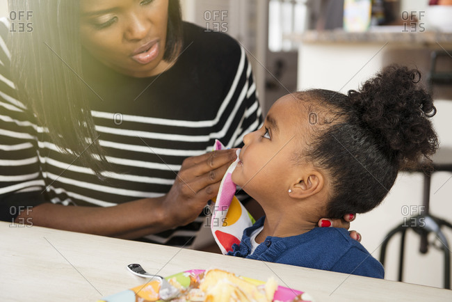 Mother wiping her young daughter's mouth with a napkin