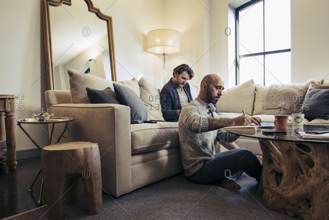 Man sitting on sofa while his partner works on laptop computer
