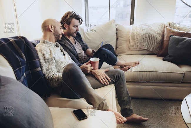 Romantic gay couple relax together on sofa while watching tablet computer