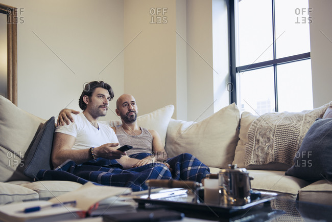 Cozy couple lounging on sofa together while watching television
