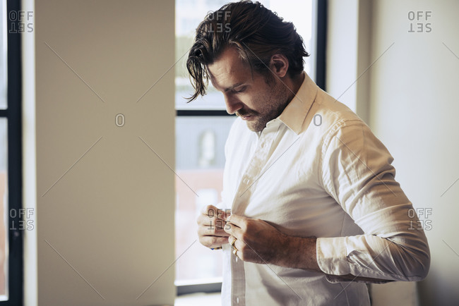Handsome man buttoning his shirt