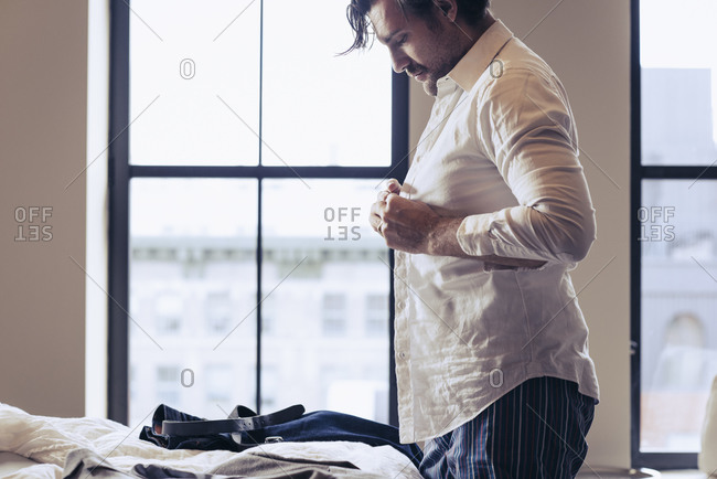 Man getting dressed in his bedroom in the morning