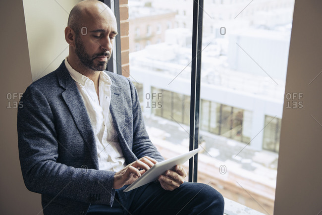 Man using tablet computer while seated in window