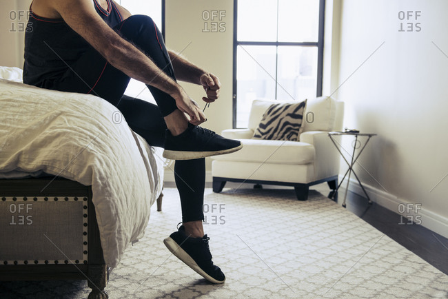 Low angle view of man sitting on bed and tying his running shoes