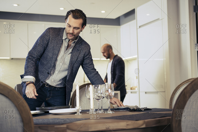 Man setting dining table while partner works in kitchen