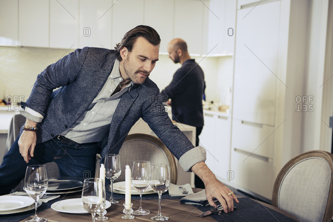 Man setting table for dinner party while his partner works in kitchen