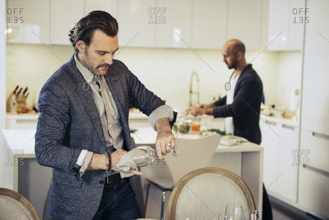 Man wiping wine glass while his partner prepares food in kitchen
