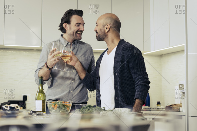 Romantic couple toasting with wine glasses in kitchen