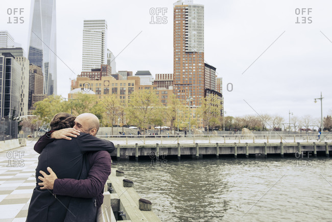 Couple hugging along Lower Manhattan waterfront with Freedom Tower in background