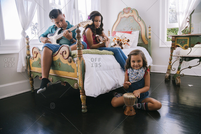 Three children playing music together in bedroom