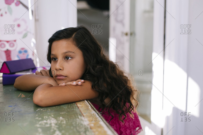 Beautiful young girl resting her head on her folded arms on table while lost in thought