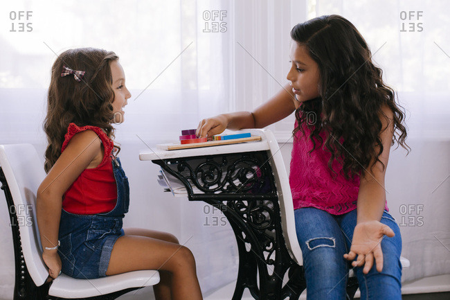 Girl helping her younger sister with puzzle