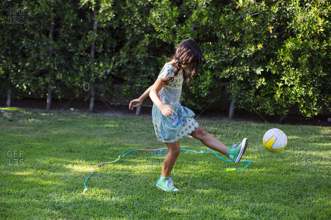 Girl kicking soccer ball in backyard