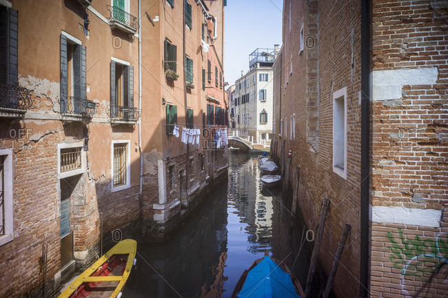 Laundry hanging from windows over canal in Venice, Italy