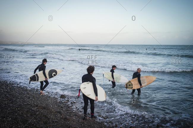 Four surfers walking into ocean on rocky beach
