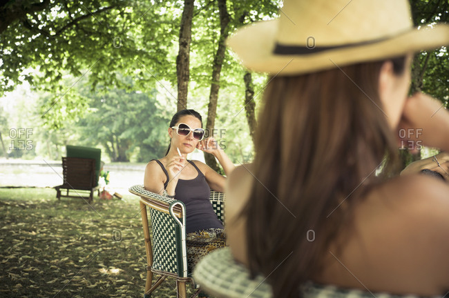 Woman in sunglasses smoking a cigarette while seated in chair under tree