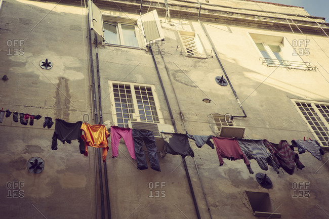 Colorful laundry hanging from windows of building in Europe