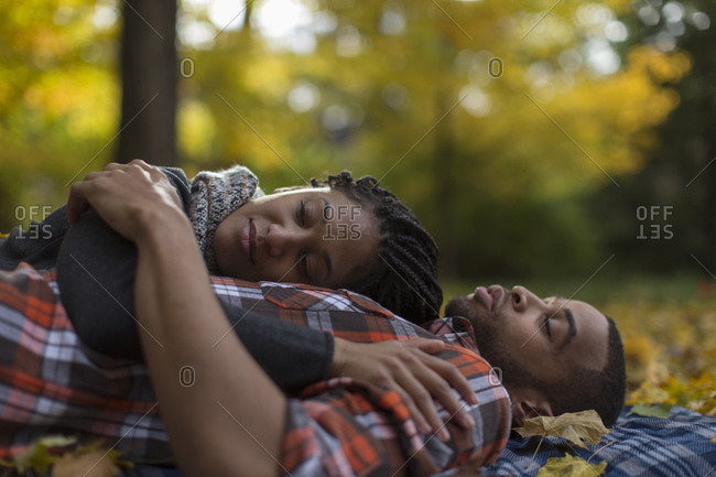 Woman resting her head on partner's chest while lying on blanket outdoors in autumn