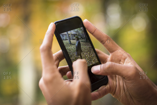 Man using smartphone to take picture of woman