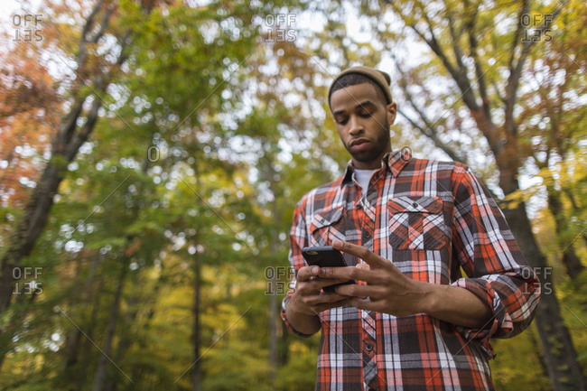 Low angle view of man using smartphone outdoors in autumn