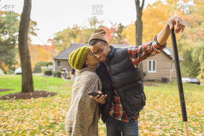 Woman kisses her partner who is using his cell phone while raking leaves