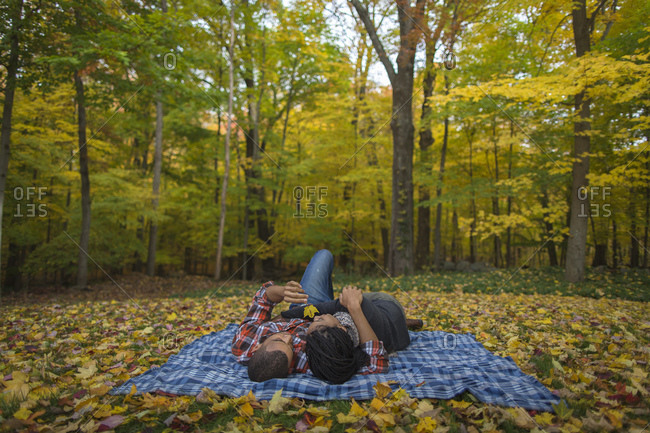 Romantic couple lying on blanket among fallen leaves in autumn