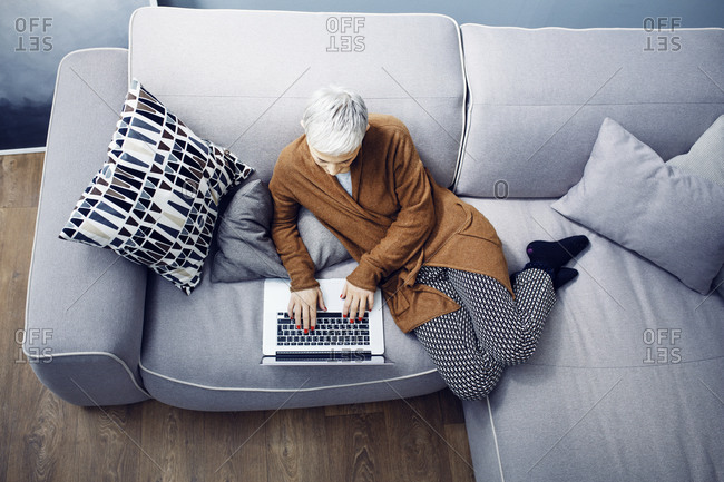 Birds eye view of a woman reclining on a sofa using a laptop