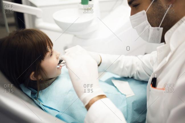 Dentist examining teeth of young girl