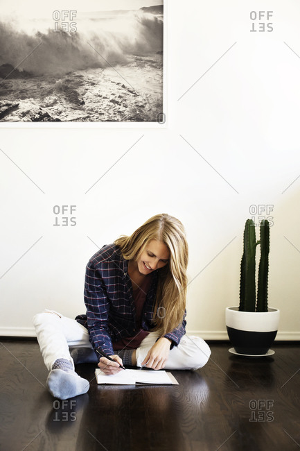 Woman sitting on the floor and writing in her journal
